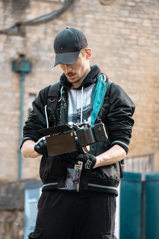 man in black leather jacket holding black smartphone