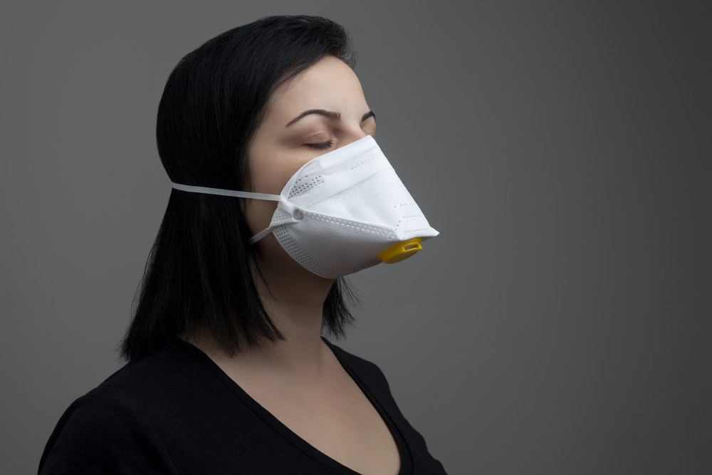 woman in black shirt with white mask