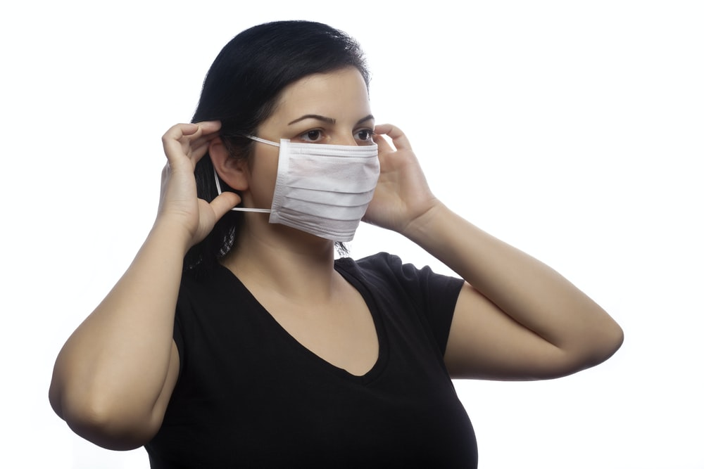 woman in black tank top covering her face with white mask