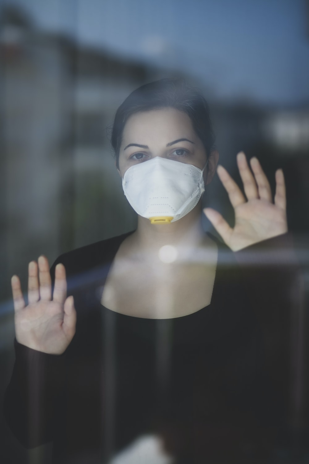 person covering face with white mask