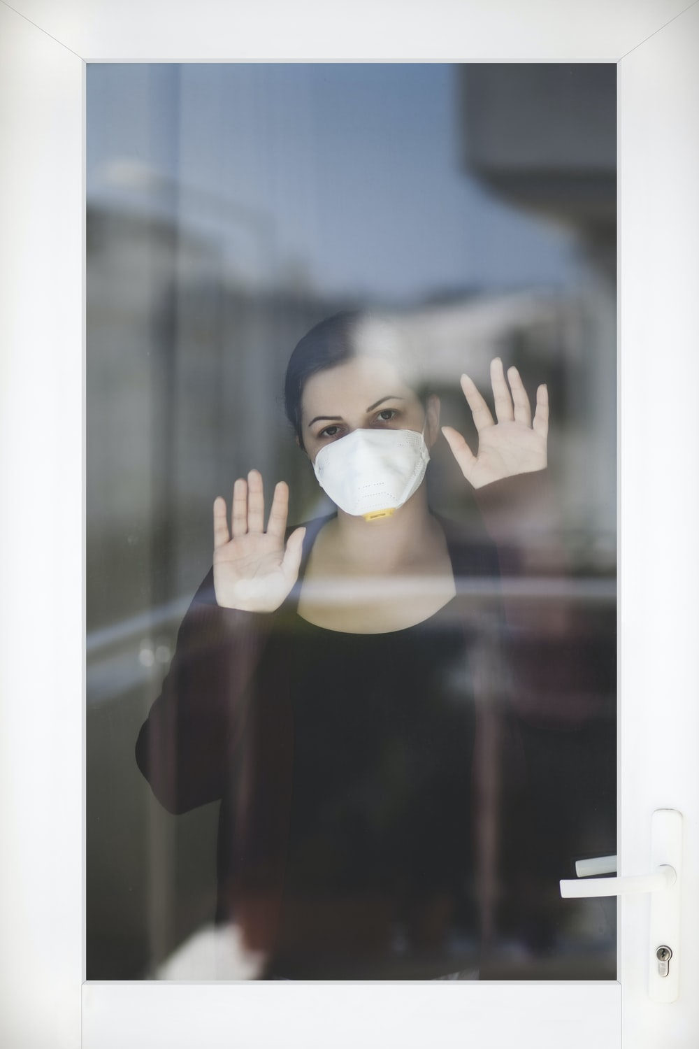 woman in red long sleeve shirt covering face with white mask