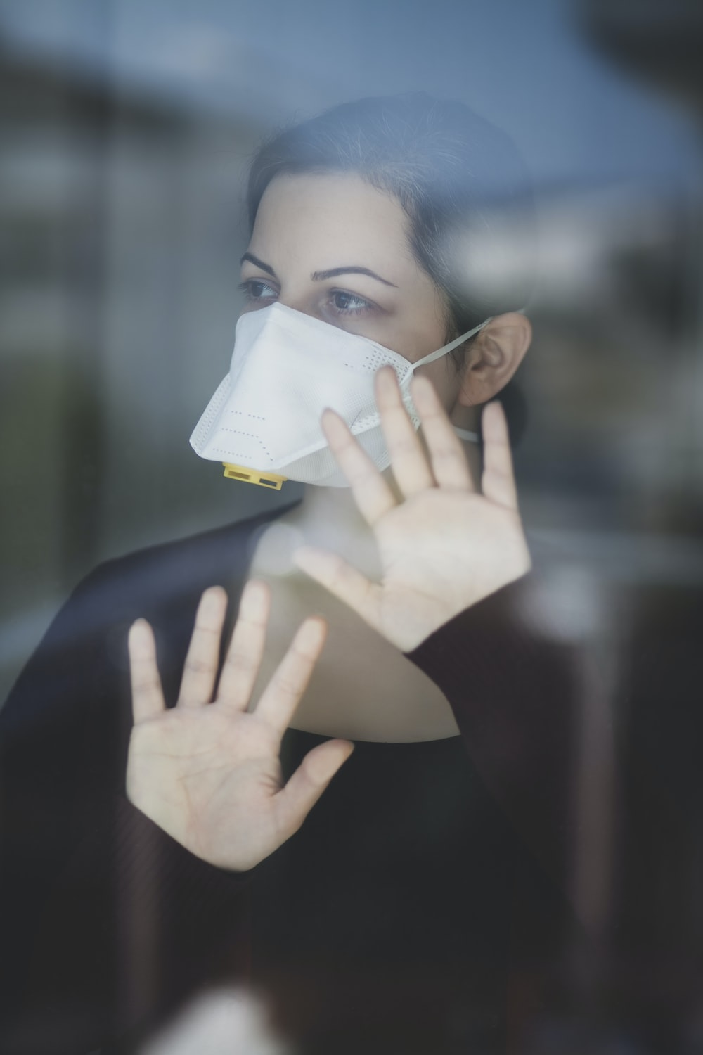 woman in black shirt covering face with white paper