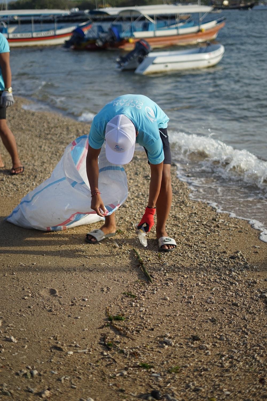 woman in white dress holding white plastic bag walking on beach during daytime