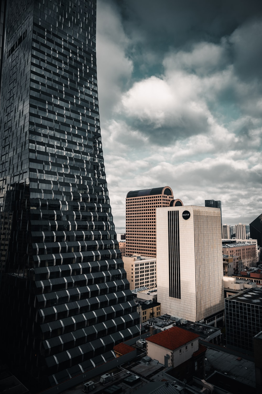 black and white concrete building under white clouds during daytime