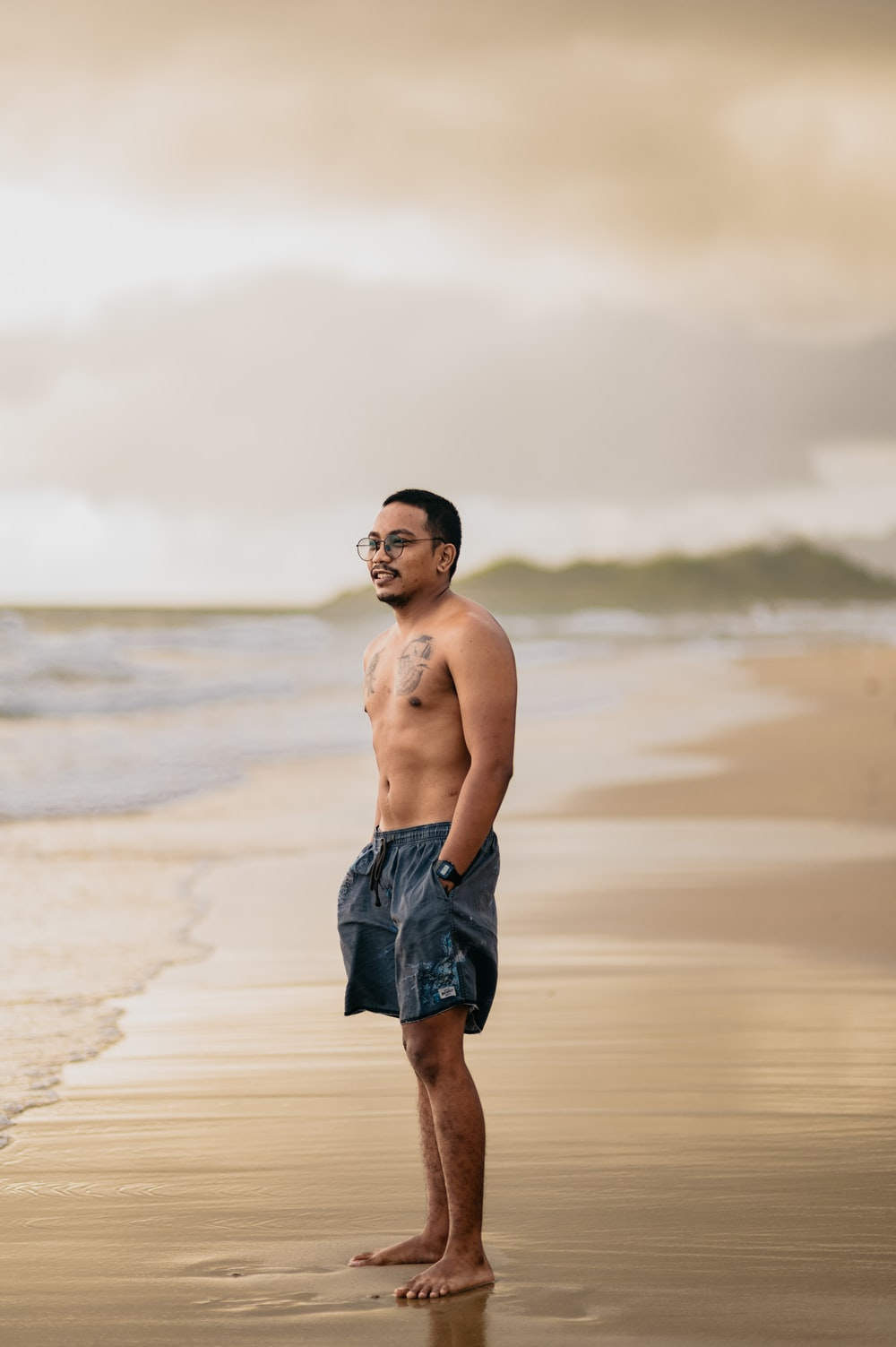 topless boy in blue shorts standing on beach during daytime