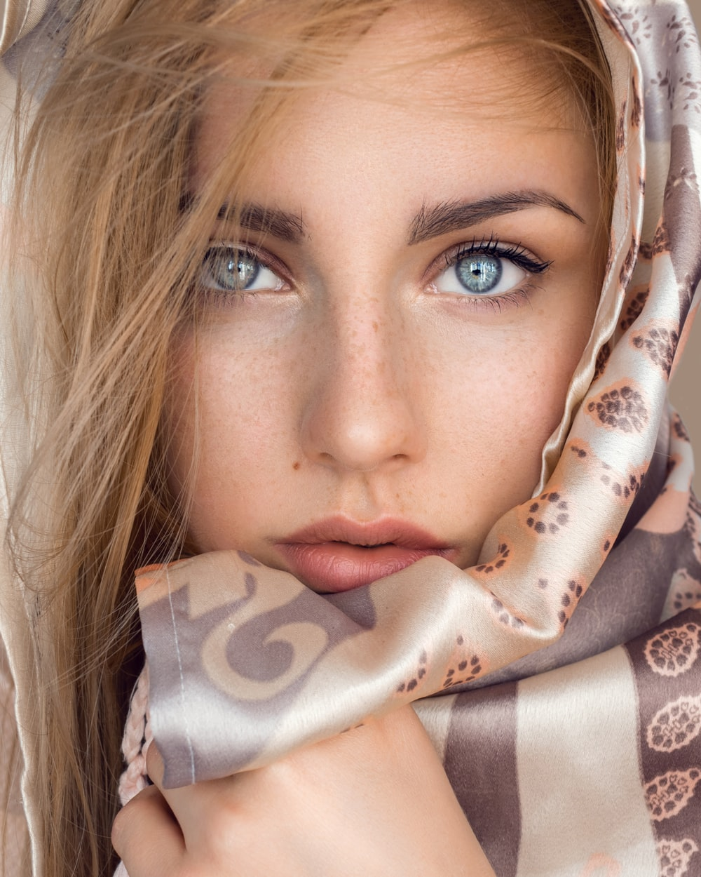 woman with brown and white floral scarf