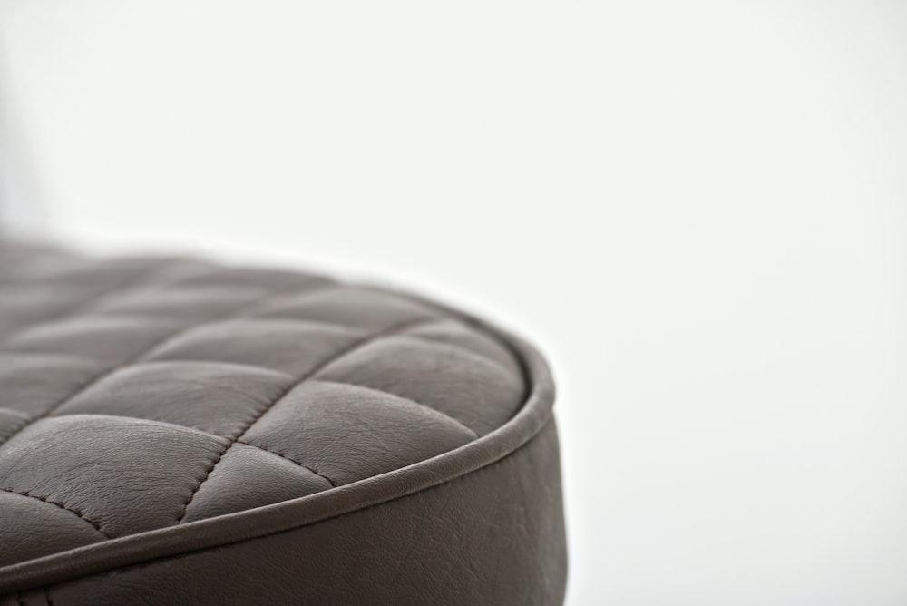 black leather round ottoman on white background
