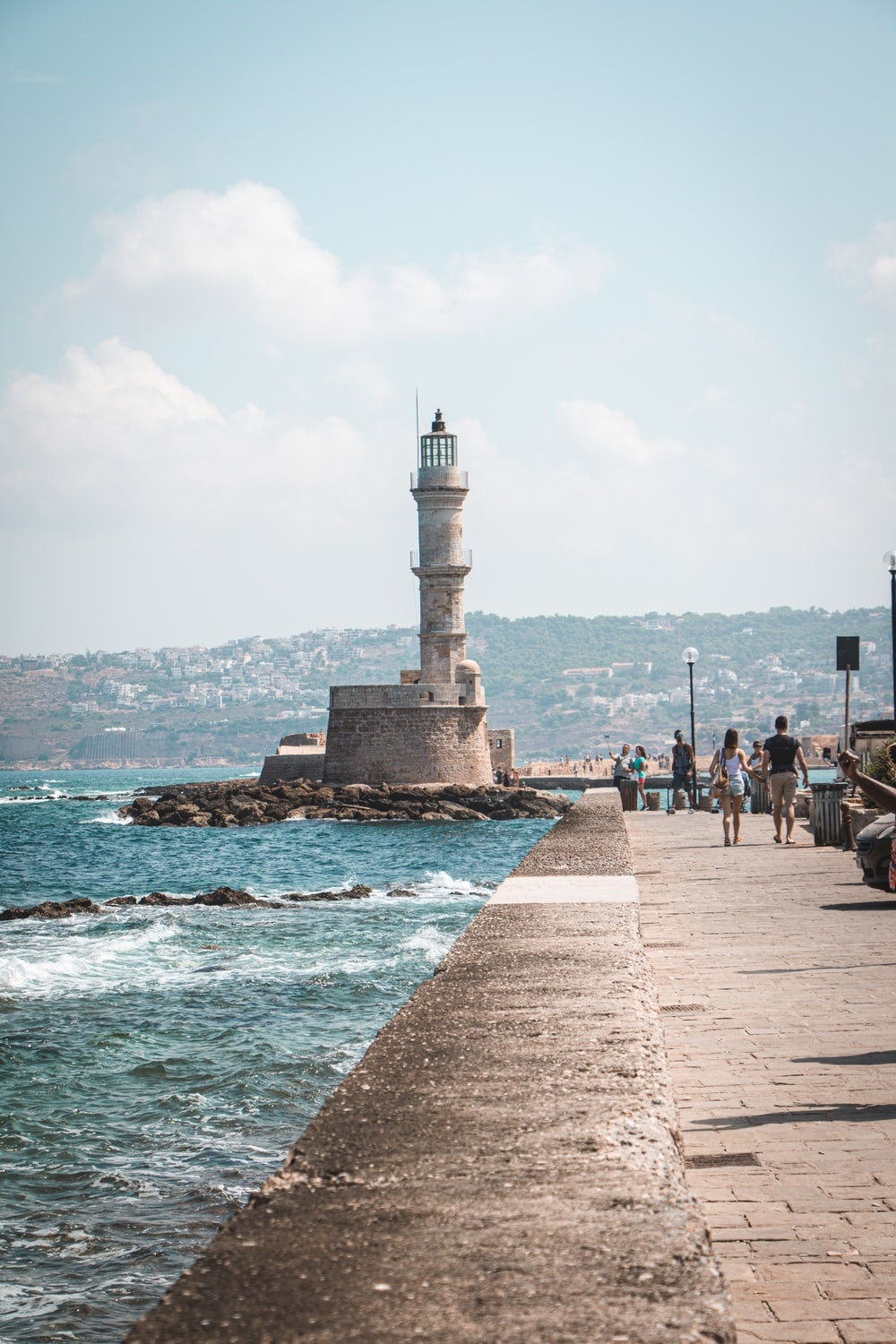 people standing near white concrete lighthouse during daytime