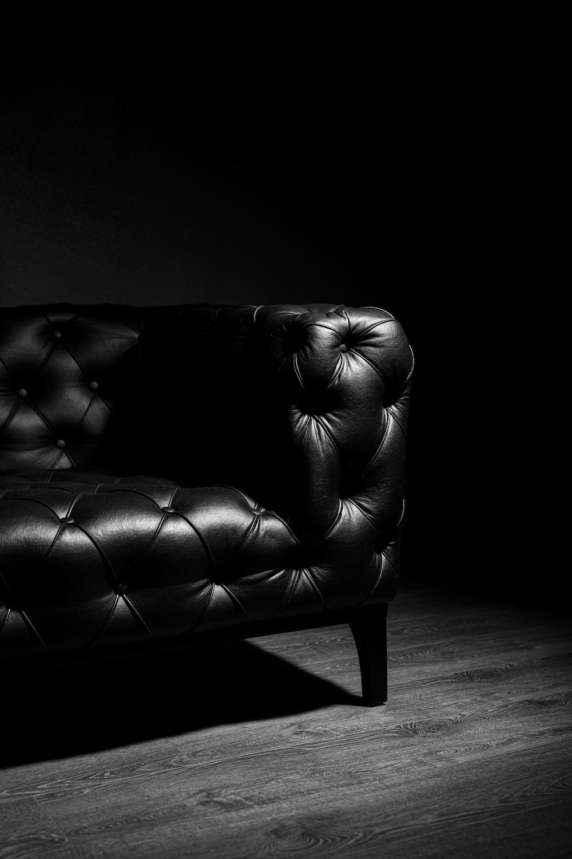 black leather loveseat on brown wooden floor