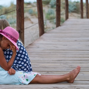 girl in blue and white polka dot shirt and pink hat sitting on wooden bridge