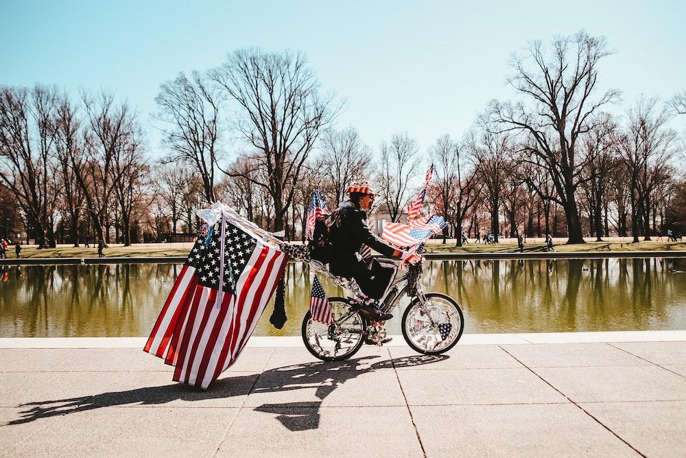 2 men riding on bicycle on road during daytime