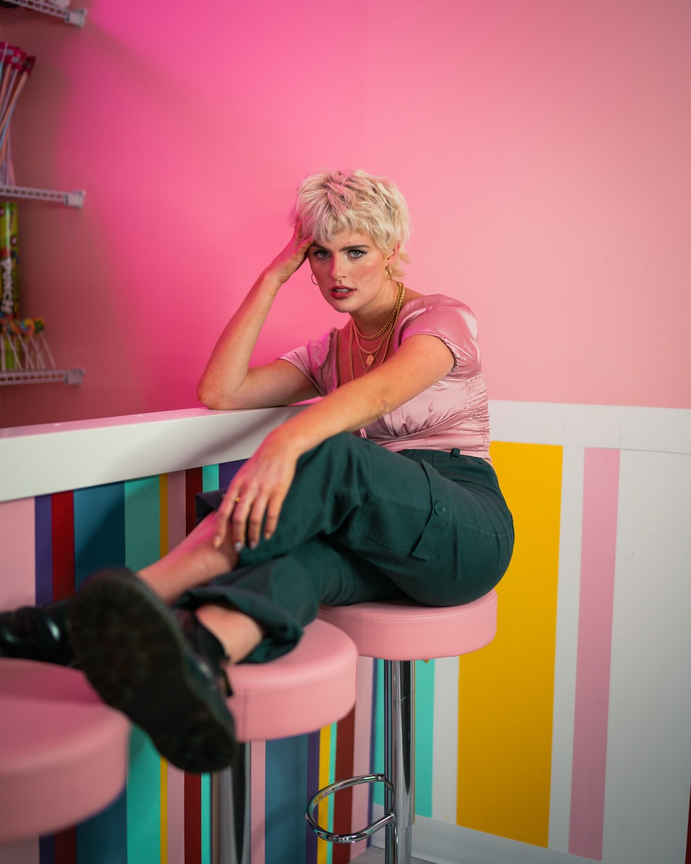woman in pink shirt and black pants sitting on white and pink wooden chair