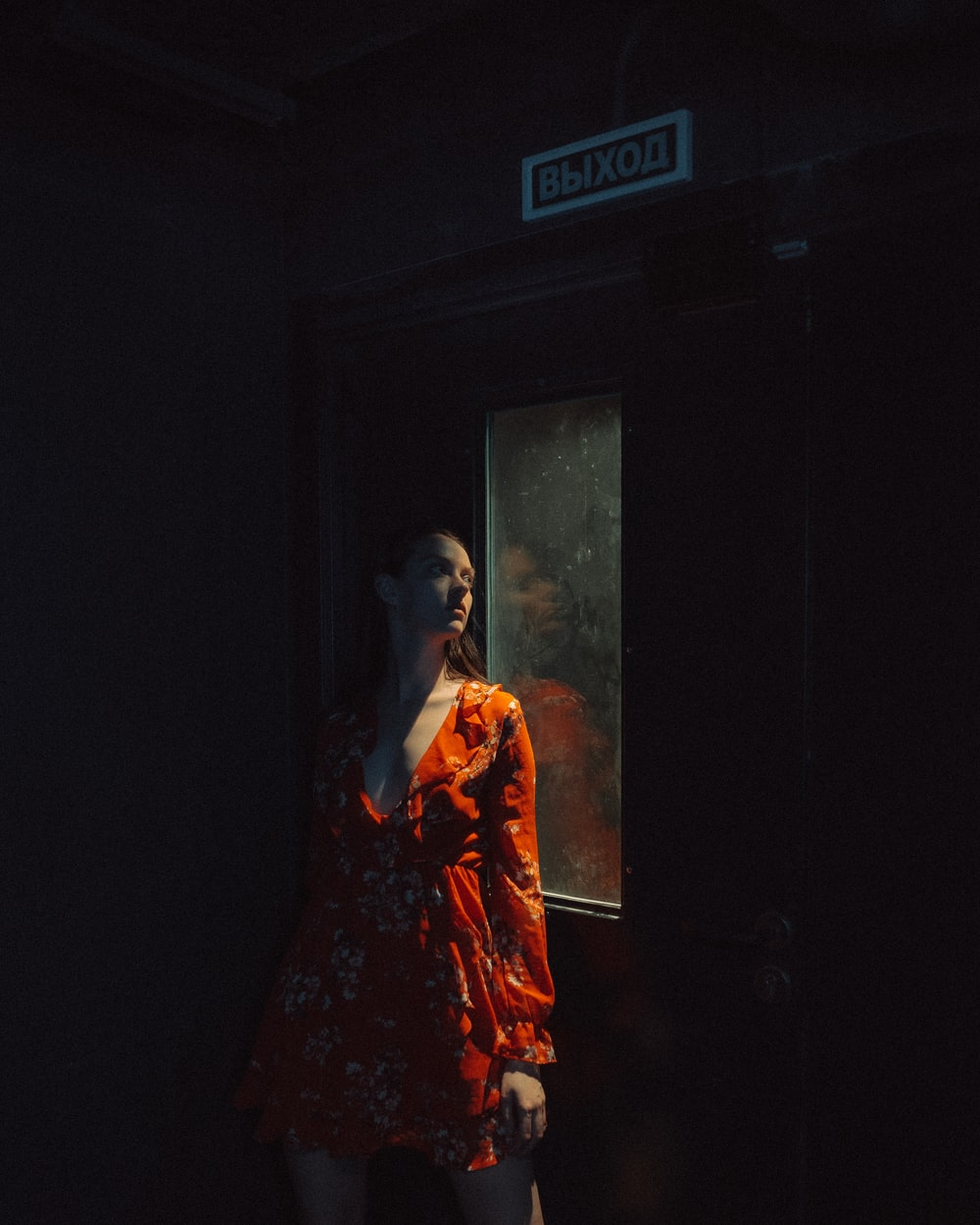 woman in red and white floral dress standing near door