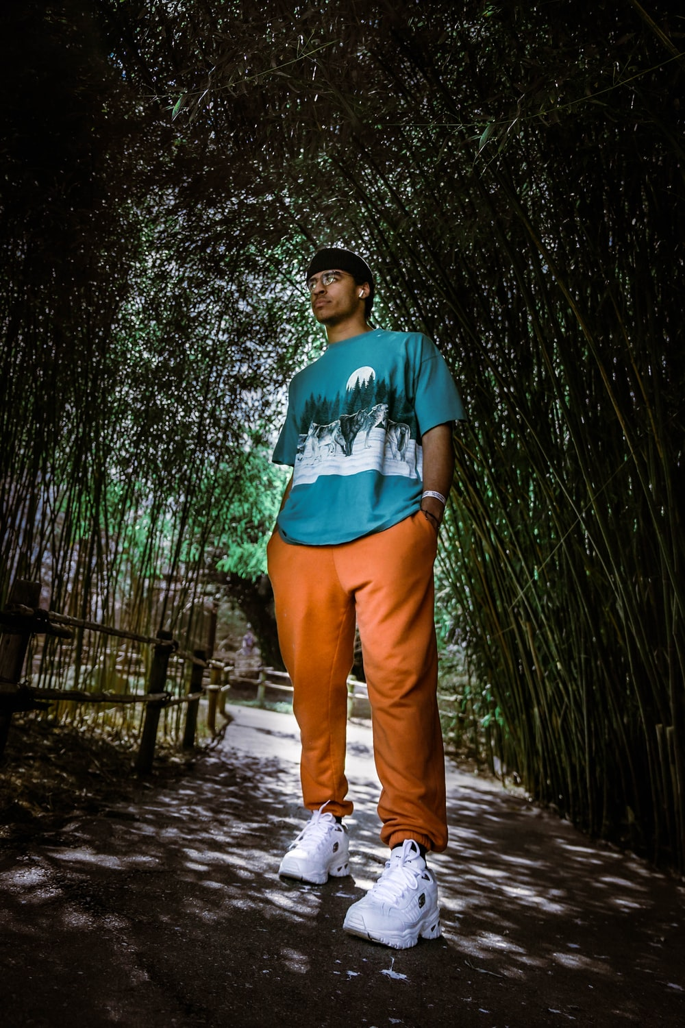 man in blue crew neck t-shirt and brown pants standing on wooden pathway