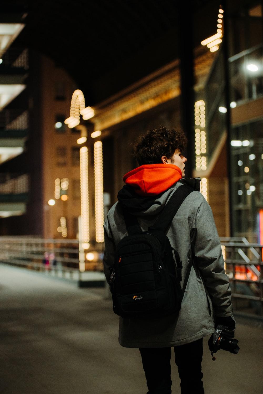 person in black and orange hoodie and black backpack walking on sidewalk during daytime