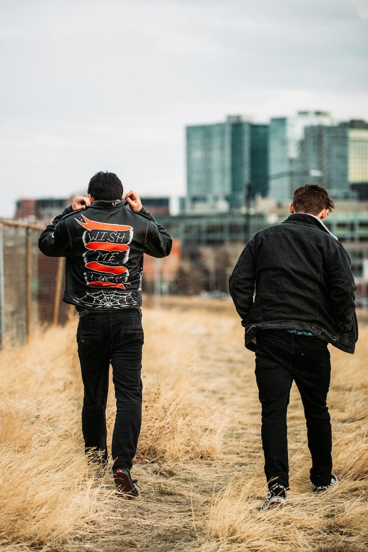 man in black hoodie standing beside man in black jacket