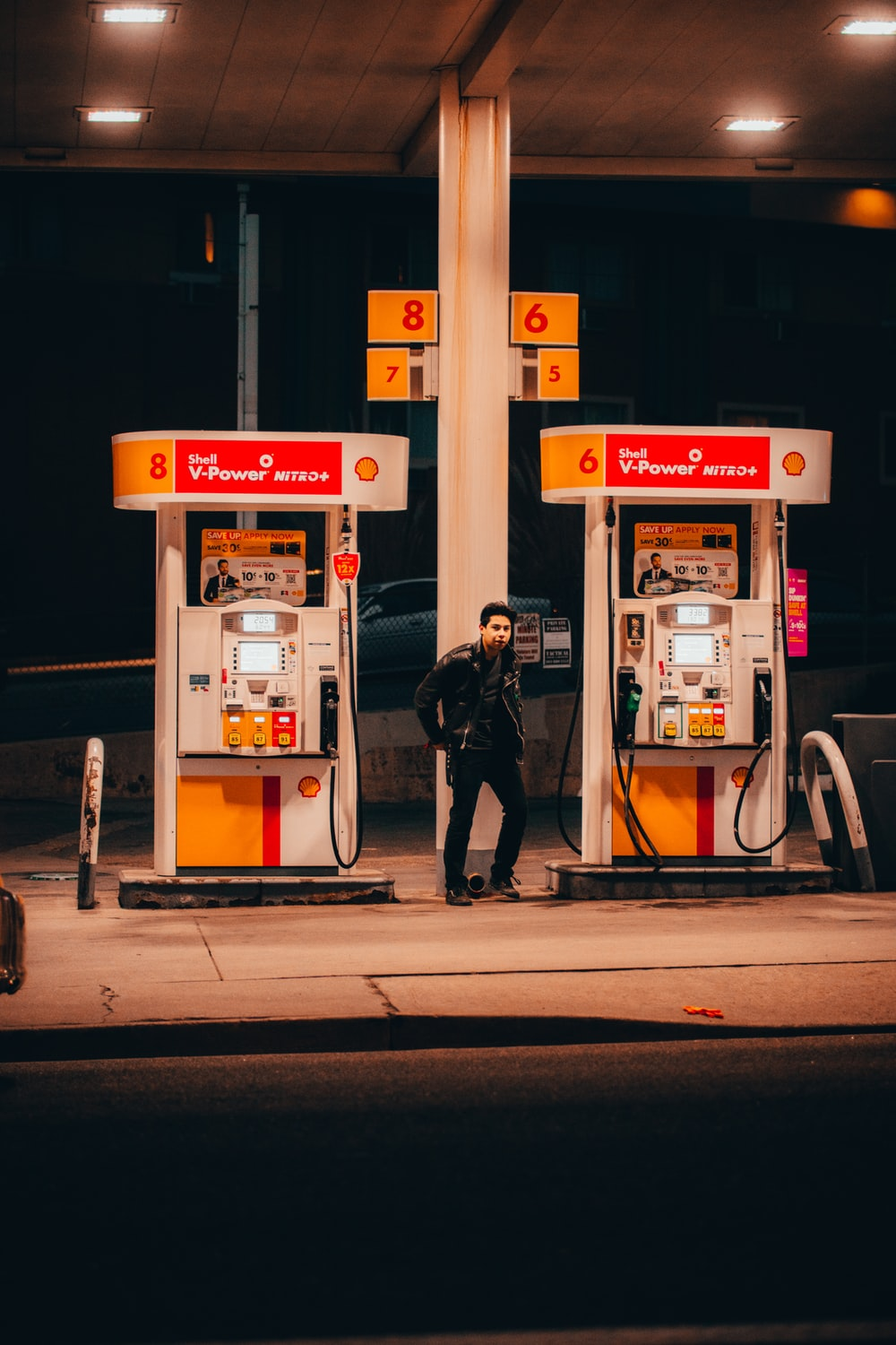 man in black jacket standing near white and red gas pump