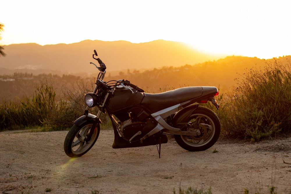 black motorcycle on brown sand during sunset