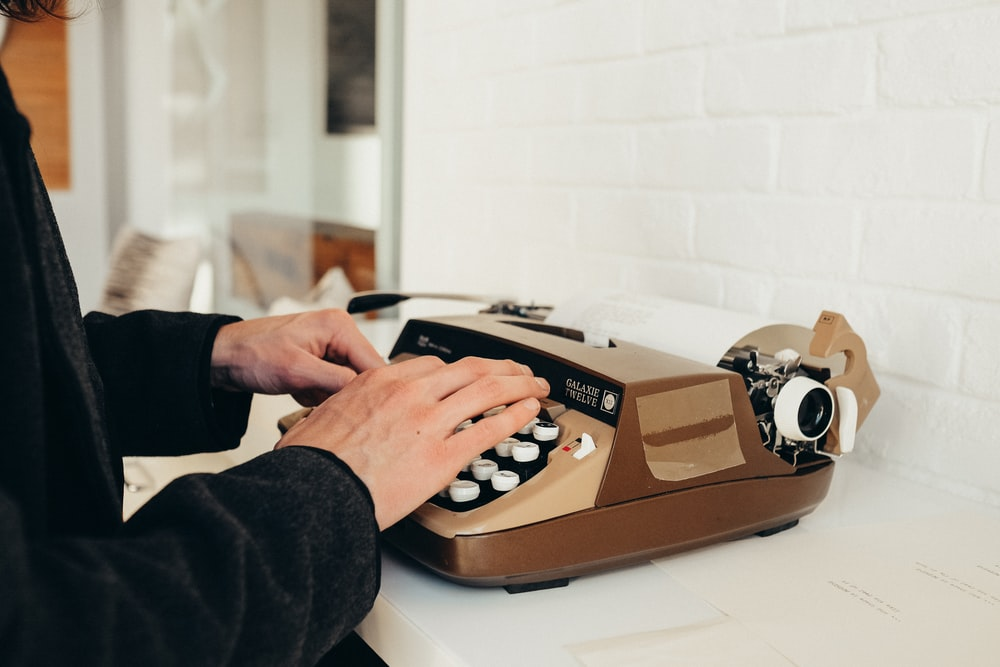 person in black long sleeve shirt using brown and white rotary phone