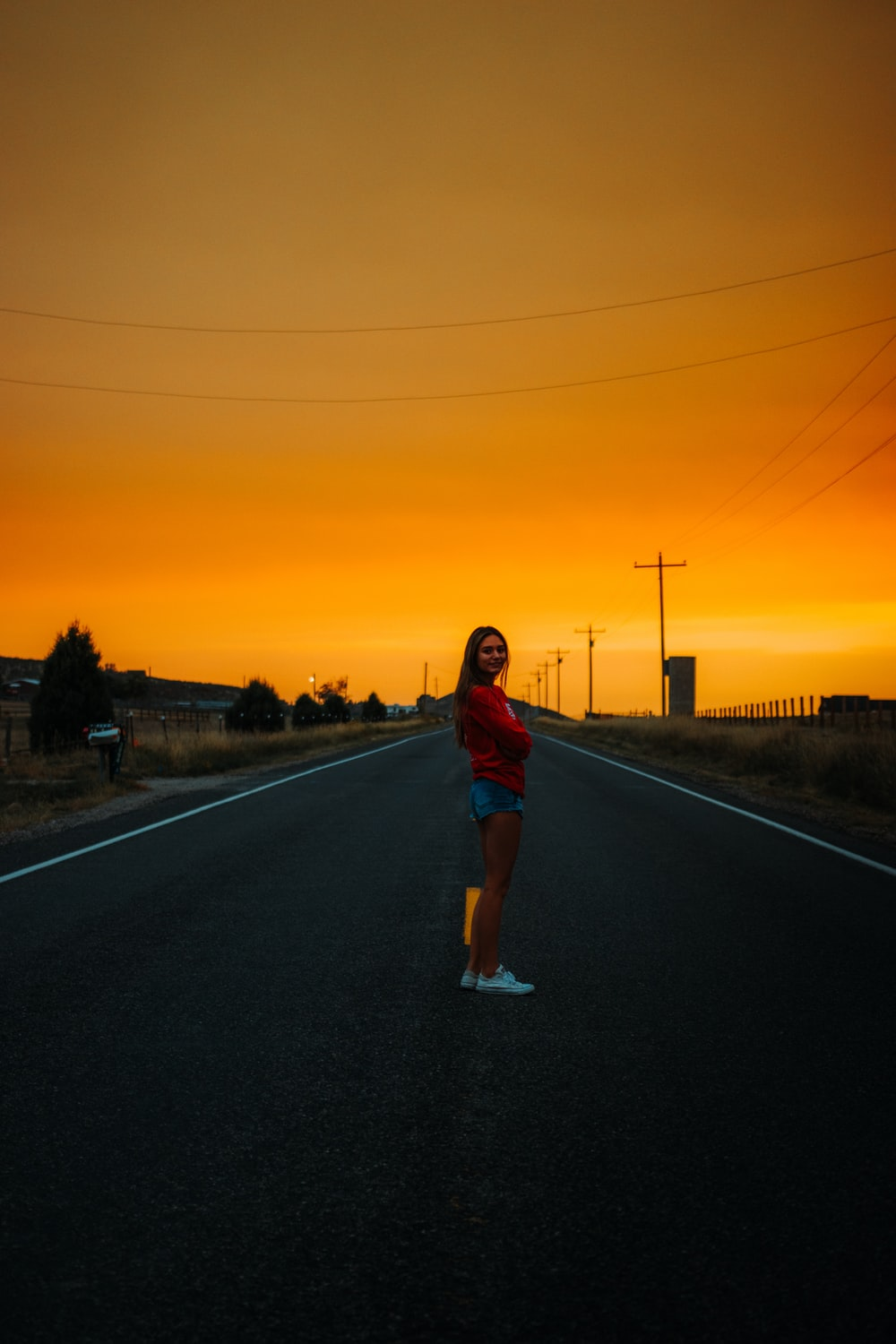 woman in red and blue plaid shirt standing on road during sunset