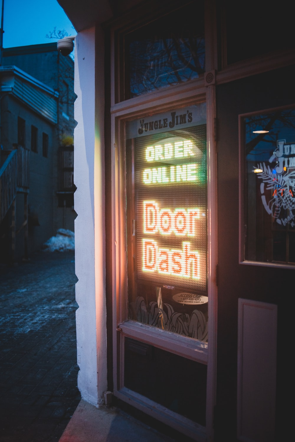 brown wooden door with red and yellow neon sign