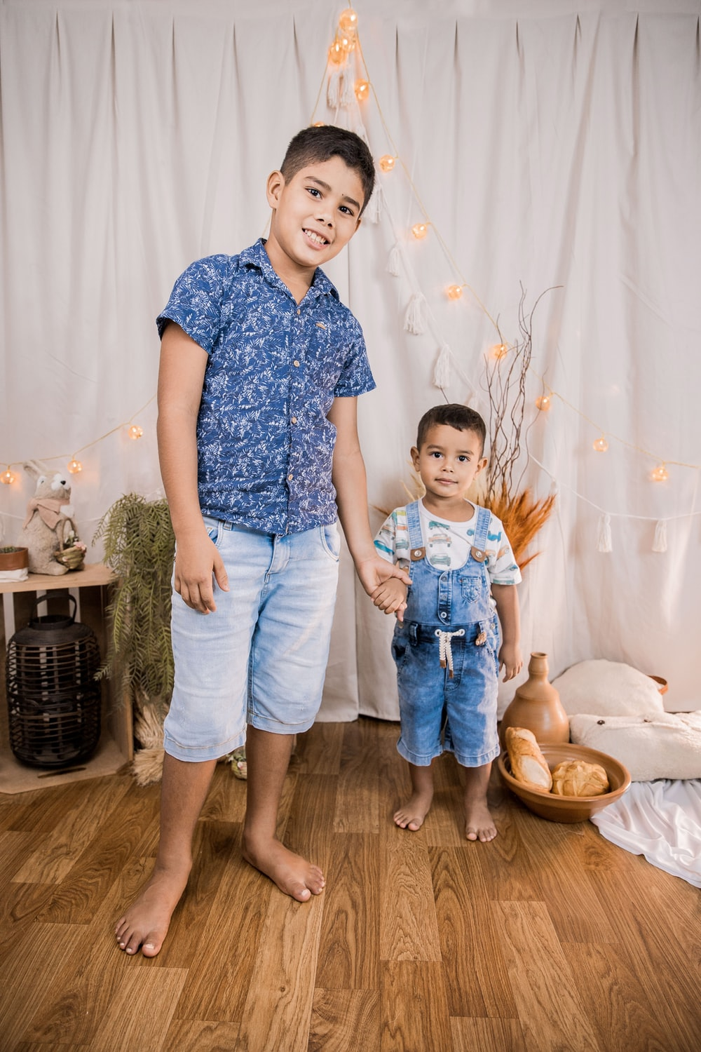 boy in blue and white floral button up t-shirt and blue denim jeans standing beside