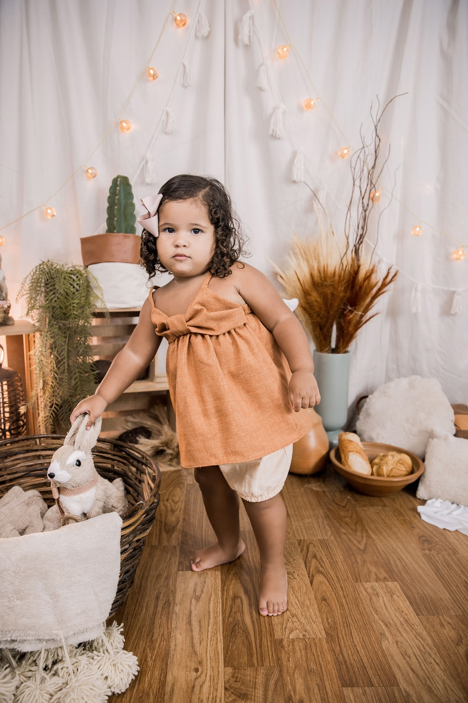 girl in pink dress standing beside white dog on brown wicker basket