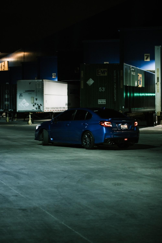 black sedan parked near white truck during night time