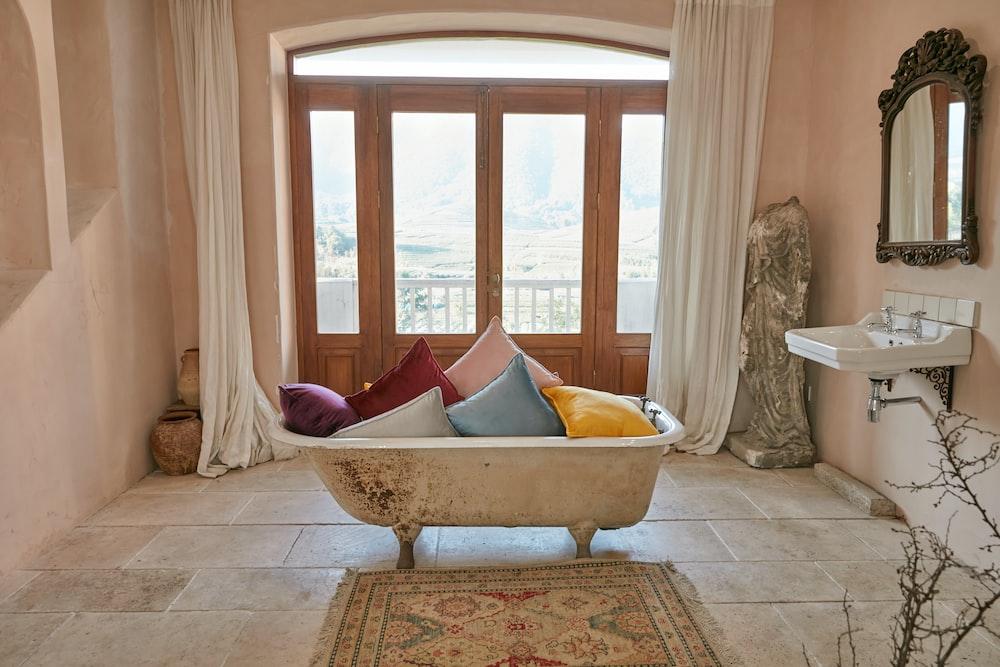white and brown bathtub near white curtains