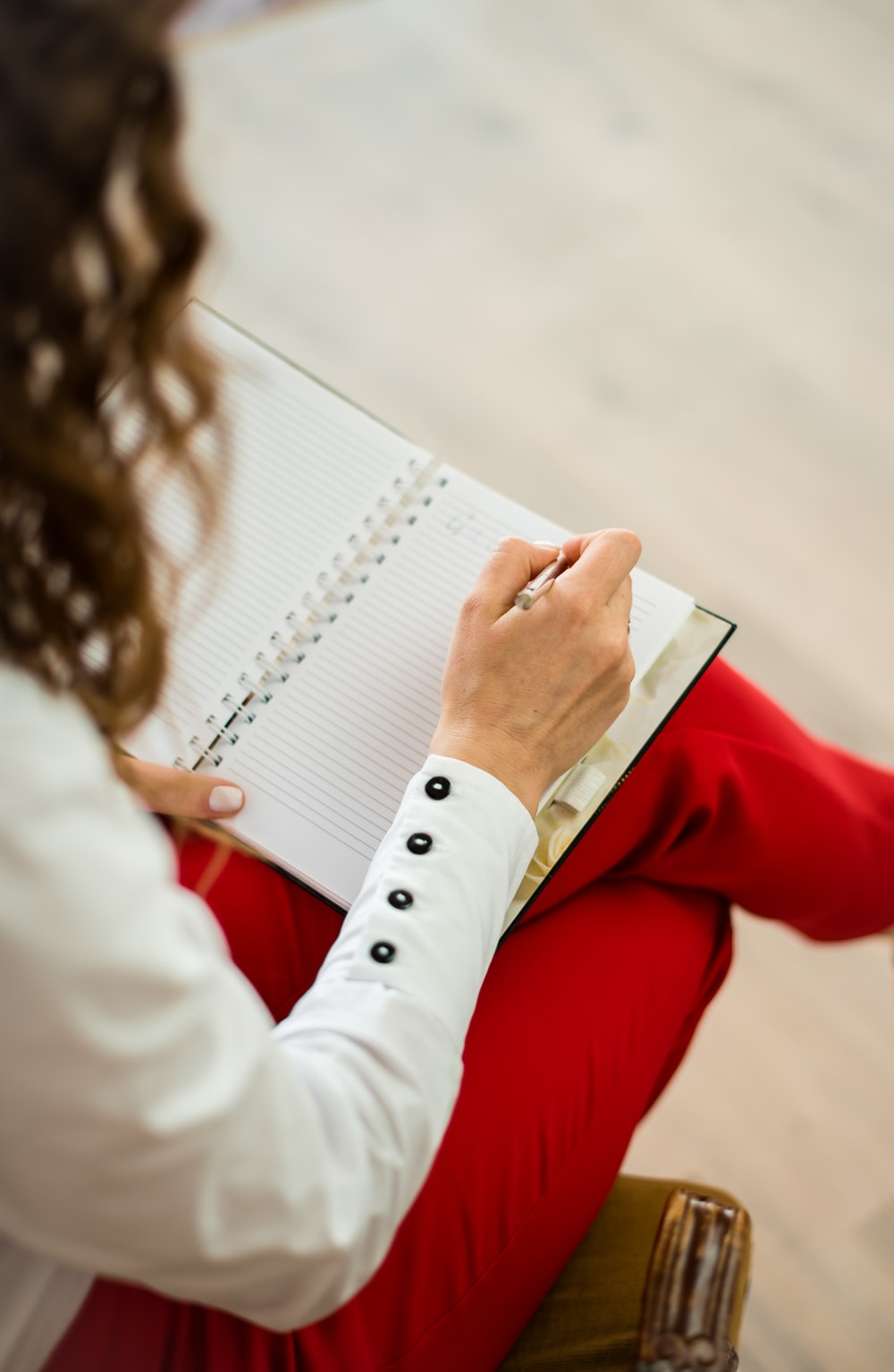 woman in red blazer holding white paper