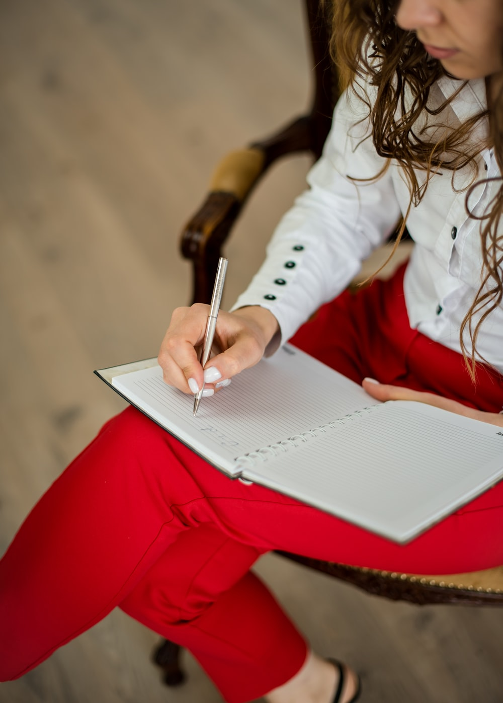 woman in white long sleeve shirt writing on white paper