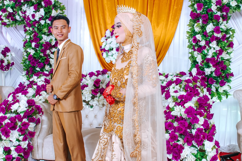 man in brown suit standing beside woman in white floral wedding dress