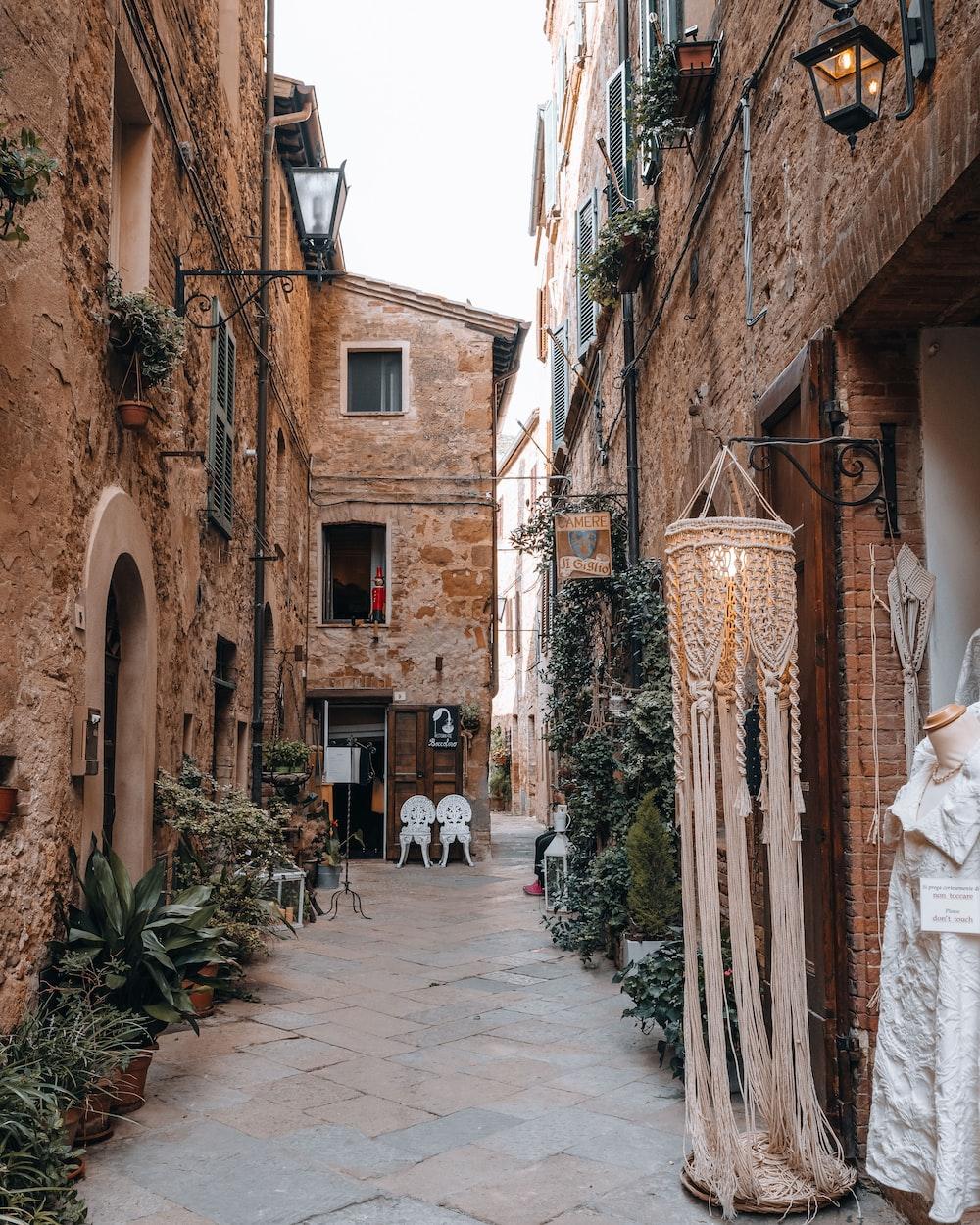 people walking on street between brown concrete buildings during daytime