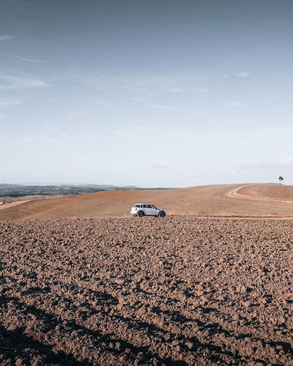 white car on brown sand during daytime