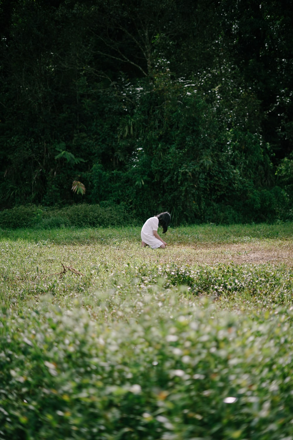 man in white t-shirt sitting on green grass field during daytime