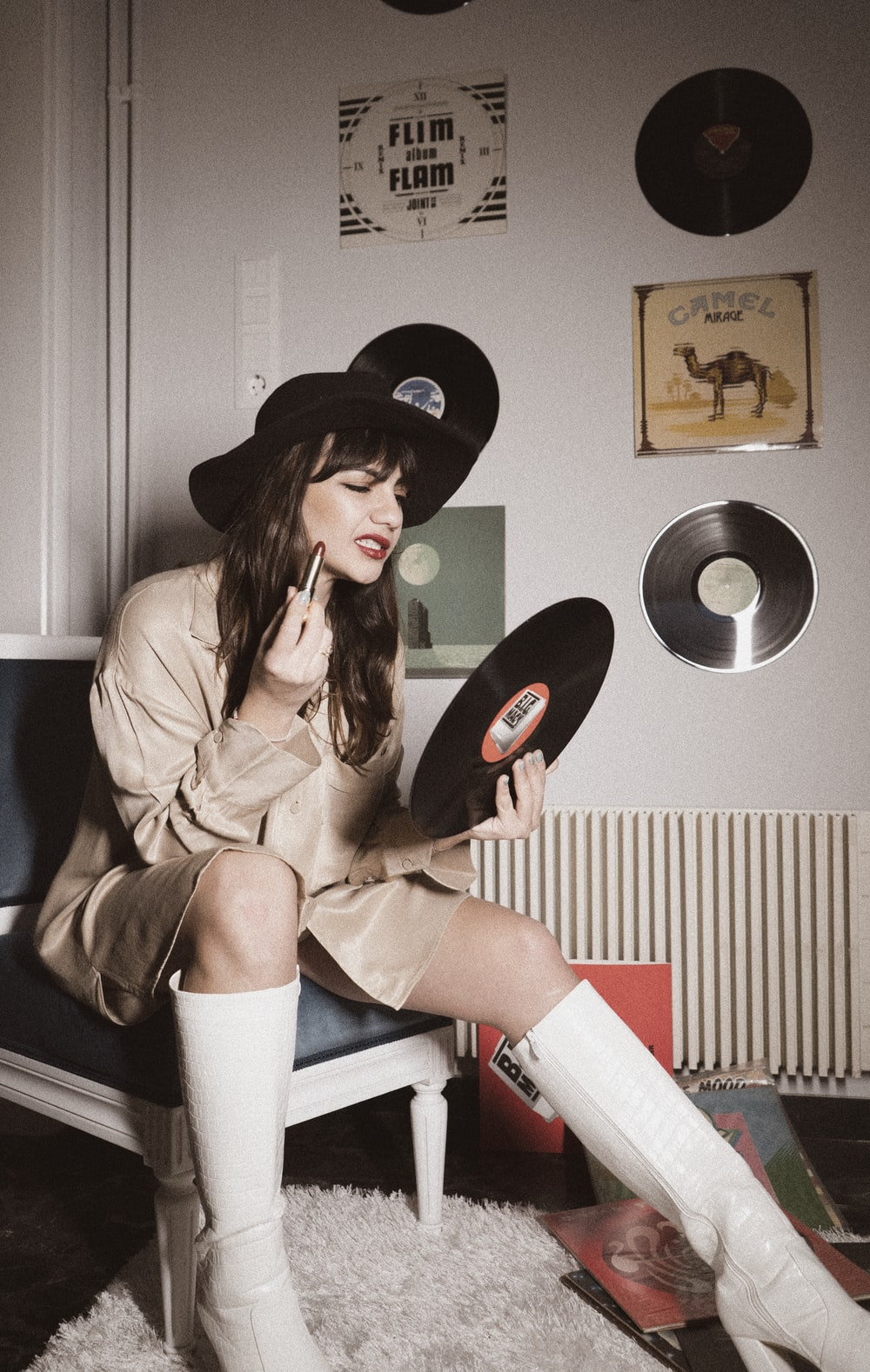 woman in brown coat and black cowboy hat sitting on white chair