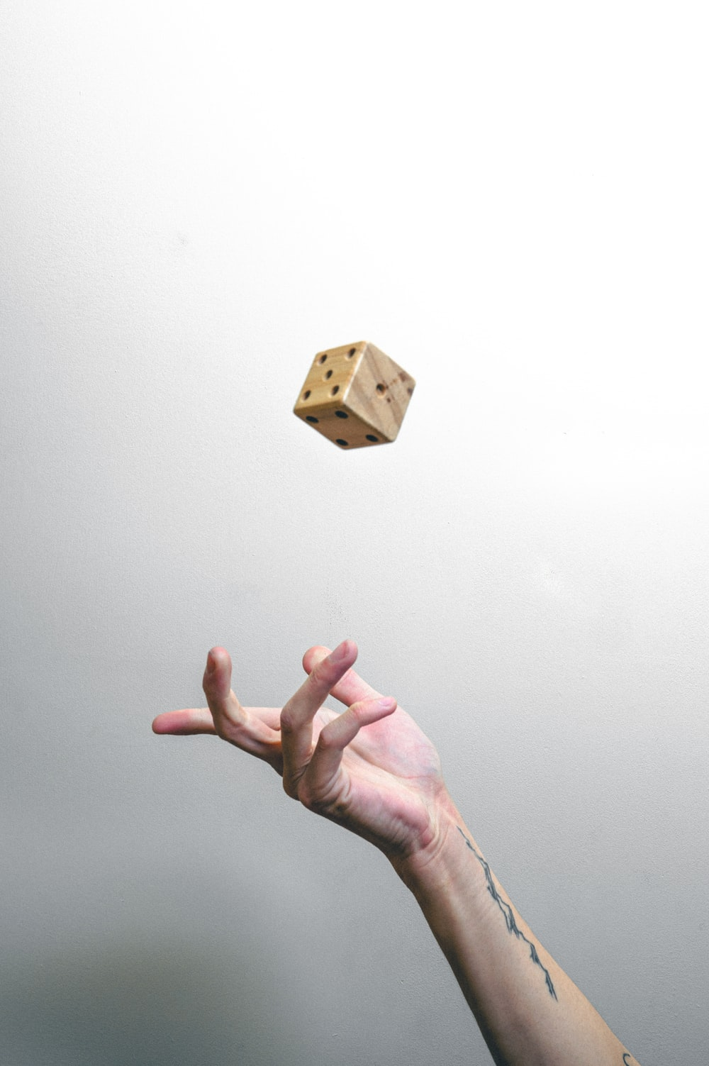 person holding brown wooden cube