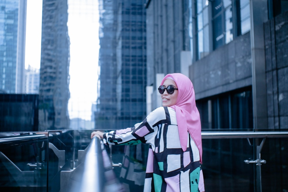 woman in pink hijab standing on the street