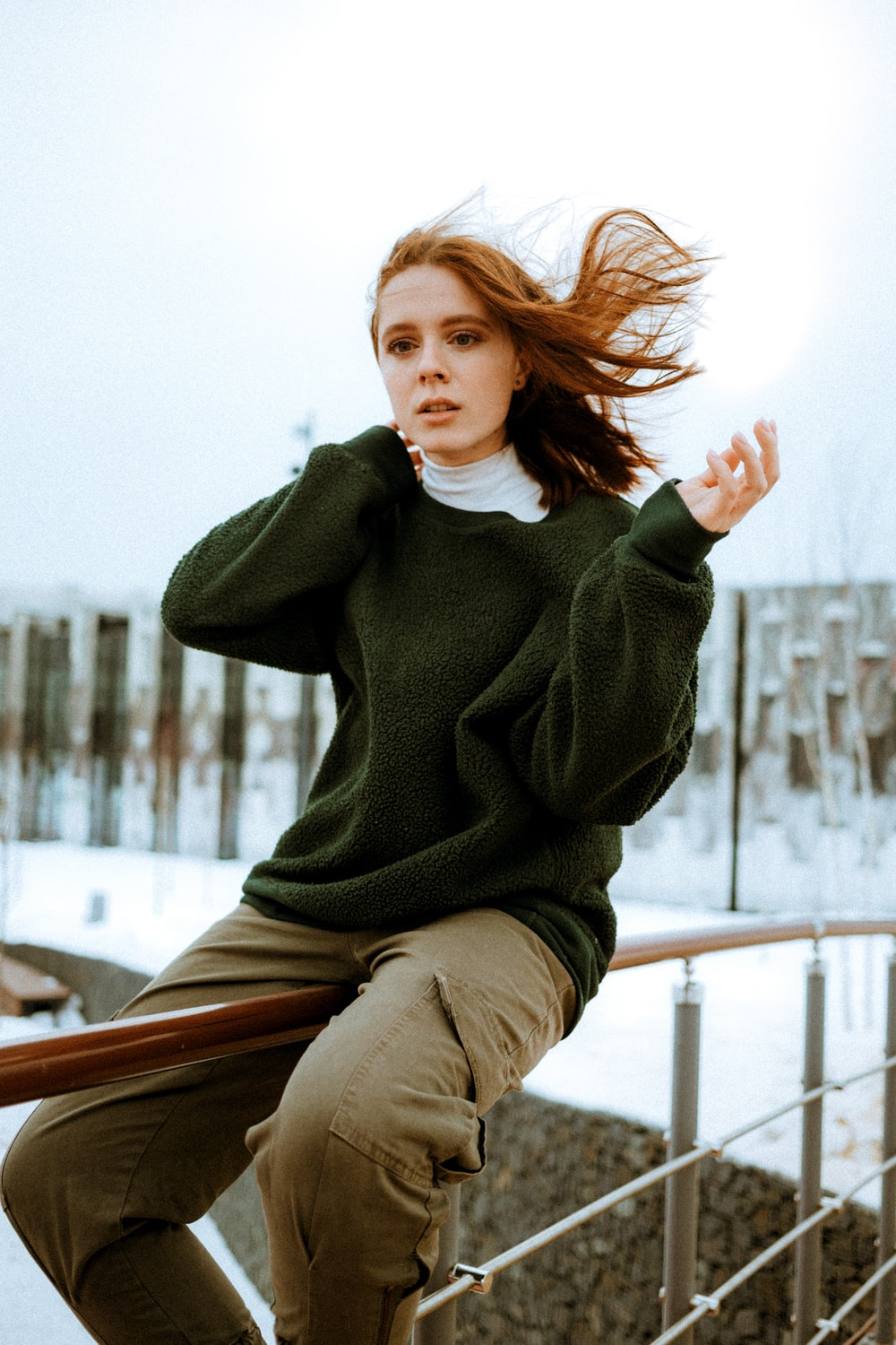 woman in green sweater sitting on brown wooden bench during daytime