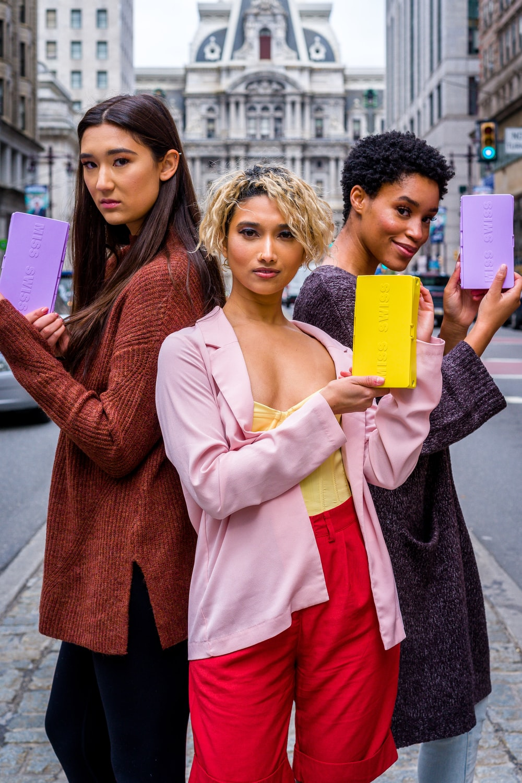 2 women holding yellow paper