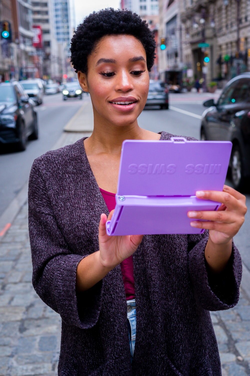 woman in gray cardigan holding pink tablet computer
