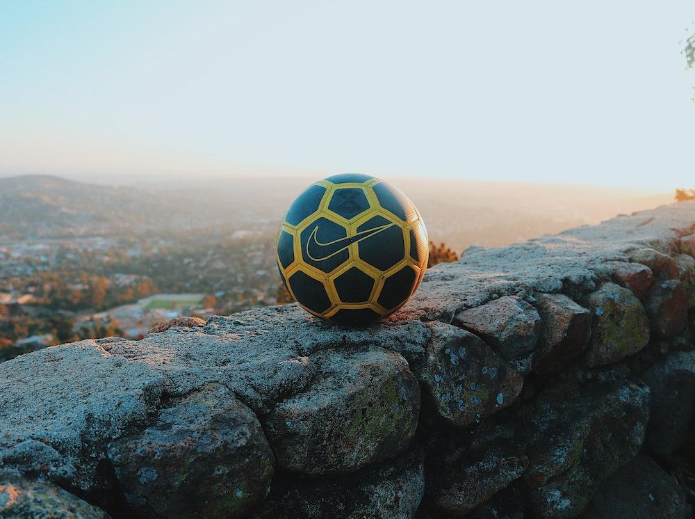 black and white soccer ball on black rock
