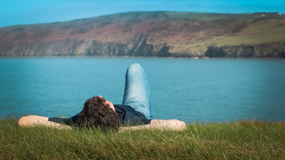 person in black shirt and blue denim jeans sitting on brown rock near body of water