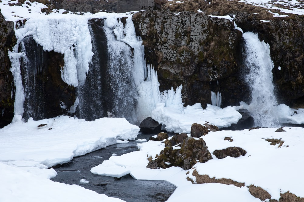 snow covered rocks and river