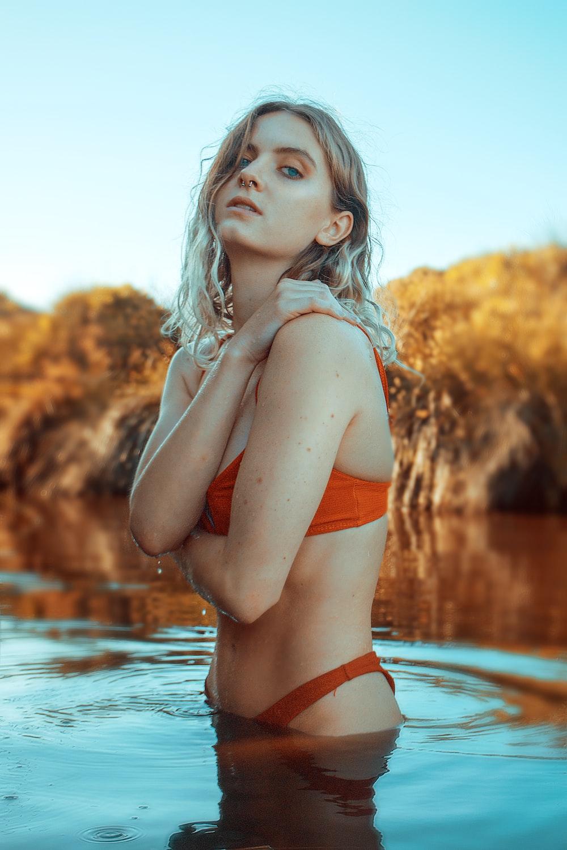 woman in orange bikini standing on water during daytime