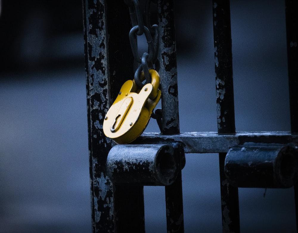 brass padlock on black metal fence