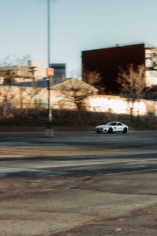 white coupe on gray asphalt road during daytime