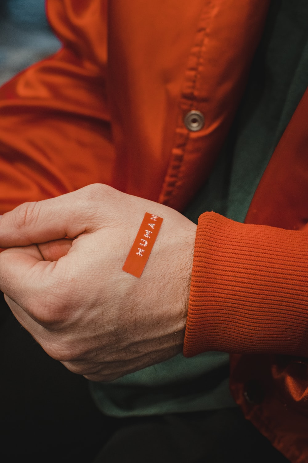 orange and white textile on persons hand