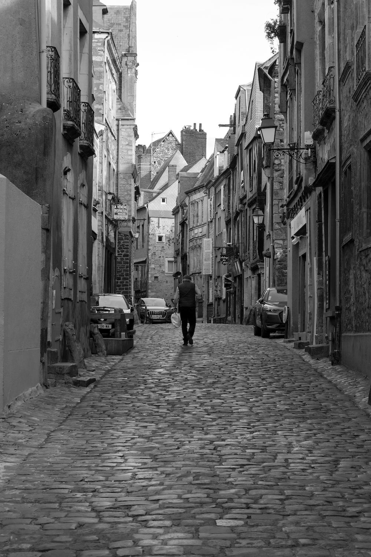 grayscale photo of man walking on street