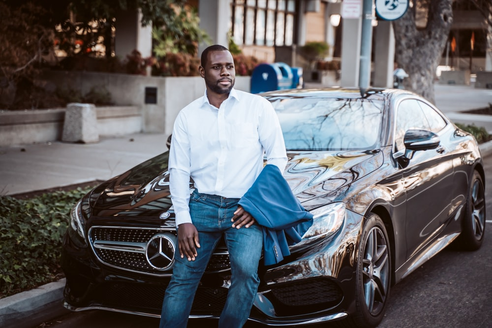 man in white dress shirt and blue denim jeans standing beside black car during daytime